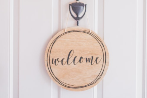 photo-of-a-white-door-with-a-hanging-wreath-and-welcome